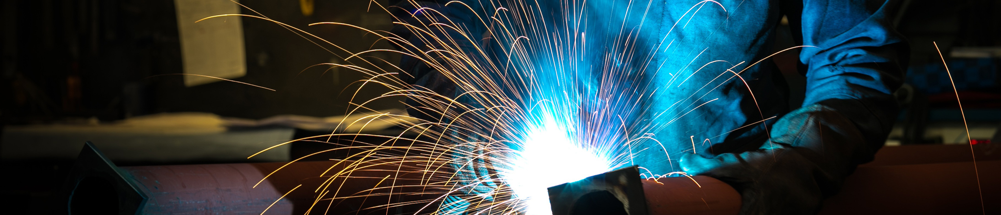 Man using welding torch to cut metal sheet in workshop.
